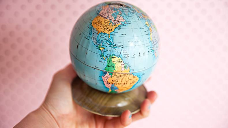 Holding a vintage French world globe money tin in hand